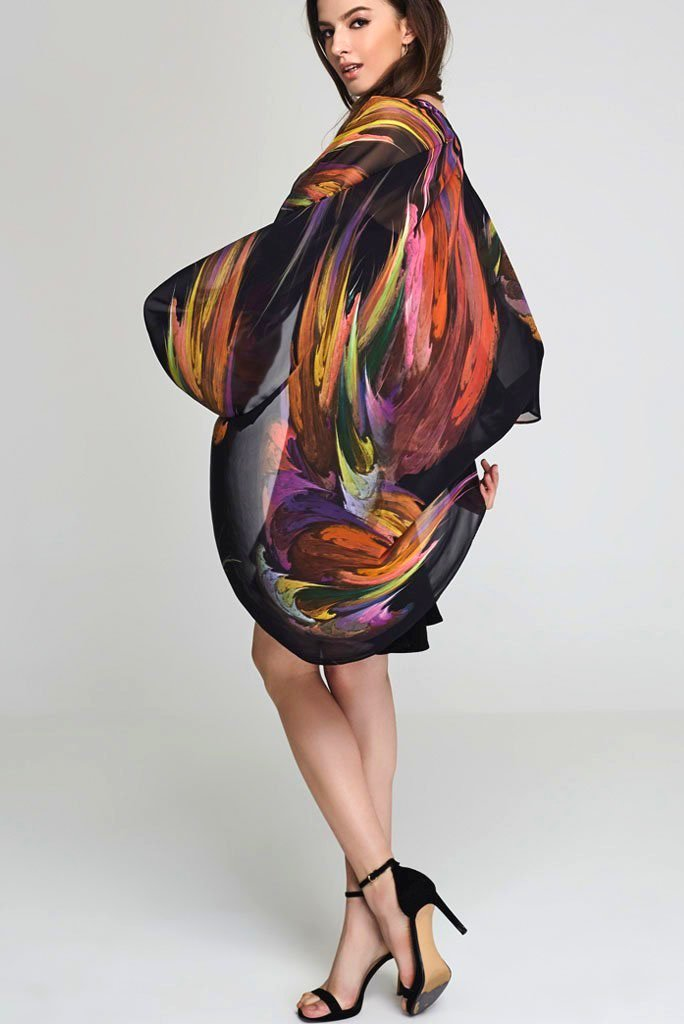 Model wearing black kimono with splashes of color facing sideways