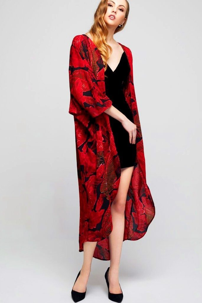 Model wearing long black crepe kimono with red leaf prints tilting her head