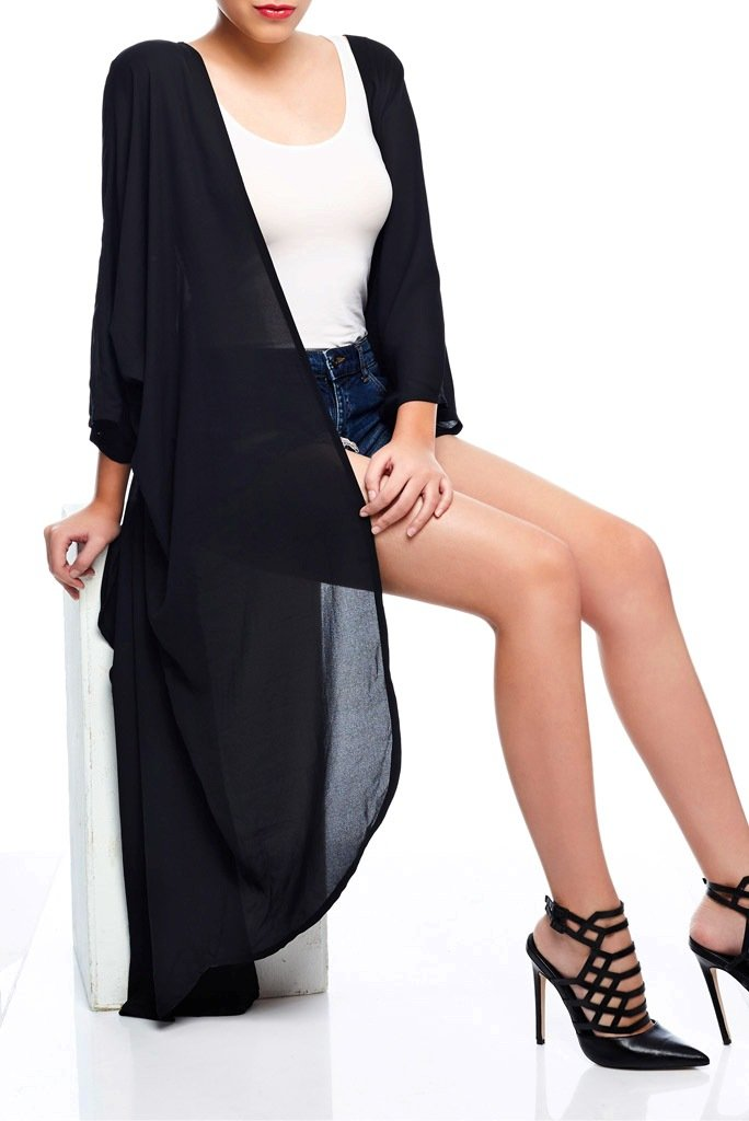 Model wearing long jet black kimono sitting down
