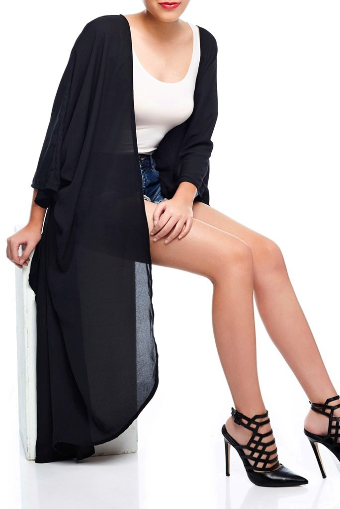 Model wearing long jet black kimono seated down