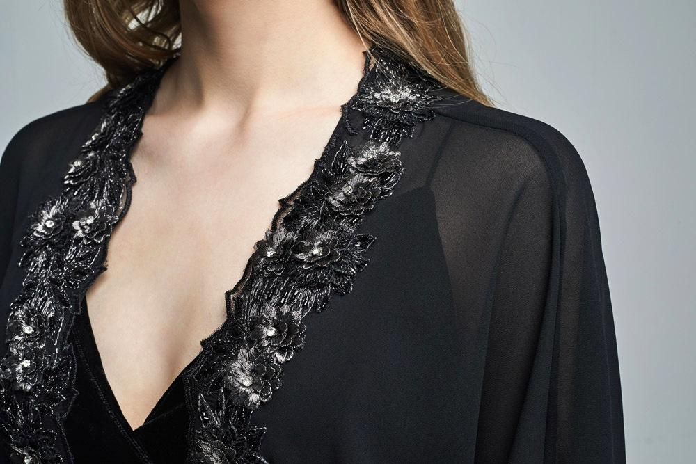 Close up of a black kimono with floral embellish & gem stones