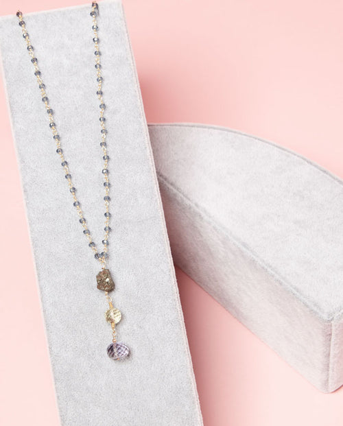 Sparkling silver, lemon and violet gems suspended from a delicate blue-beaded chain