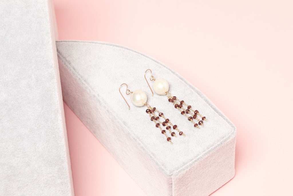 white pearls with streaming dark cherry gemstone beads earrings on box