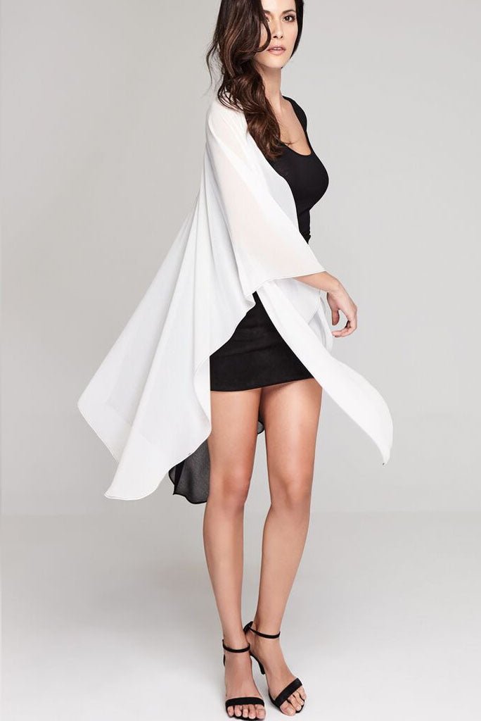 Model wearing black & white chiffon hi-lo dress facing right