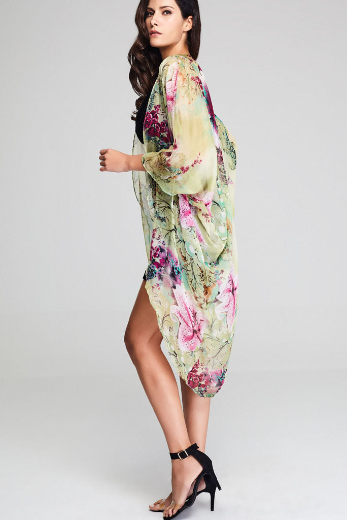 Model wearing silk kimono with floral prints facing left