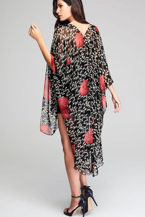 Model wearing black throw with abstract hearts