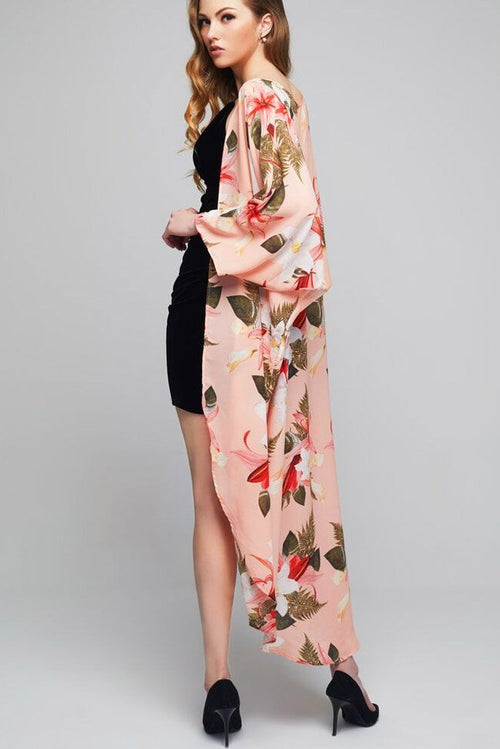 Model wearing long pink throw with floral prints facing left