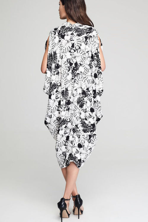 Model wearing monochrome crepe drape dress with leafy prints facing backwards