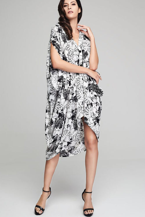 Model wearing black & white crepe drape dress with leafy prints