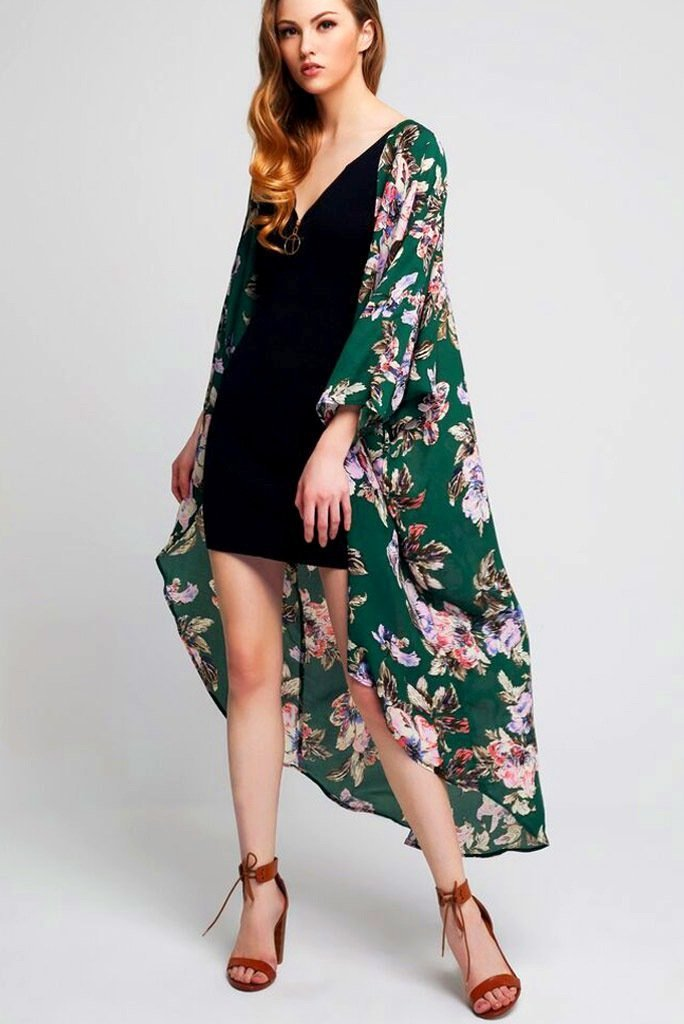 Model wearing long green kimono with floral prints facing left