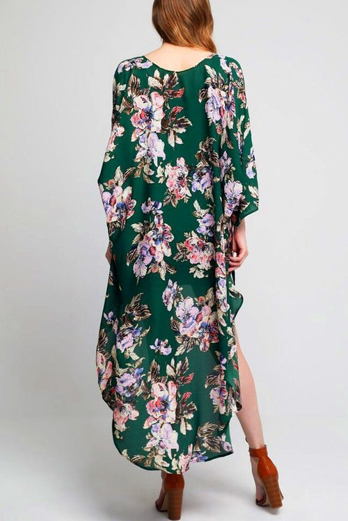 Model wearing long green kimono with floral prints facing back