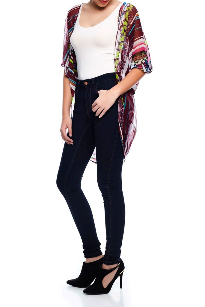 Model wearing short burgundy & pink kimono with whimsical prints facing left