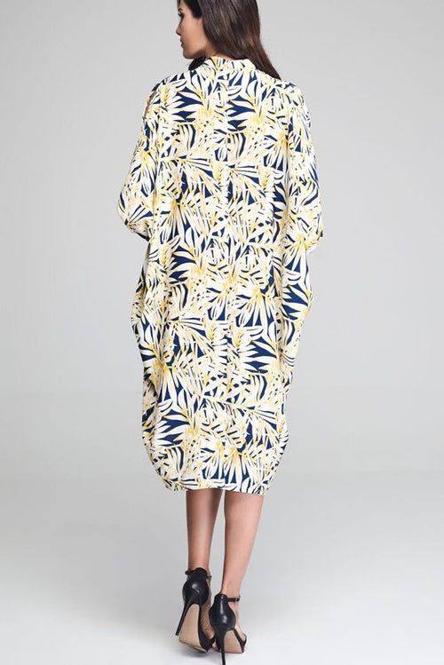 Model wearing blue drape dress with yellow leafy prints facing back