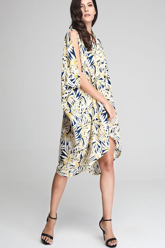 Model wearing blue crepe drape dress with yellow leafy prints facing front