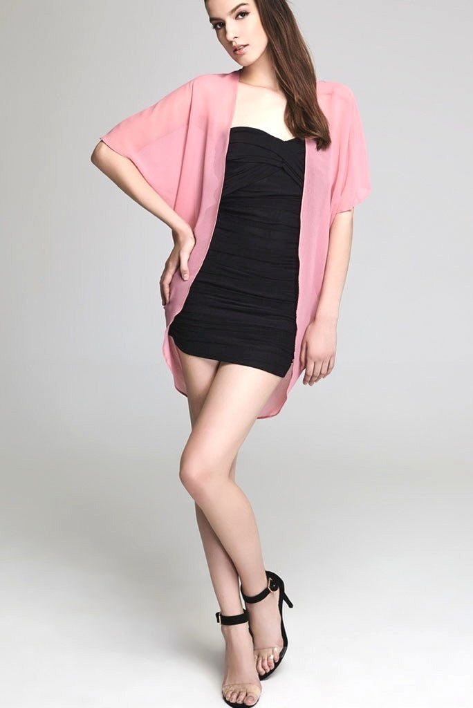 Model wearing short pink chiffon kimono facing forward