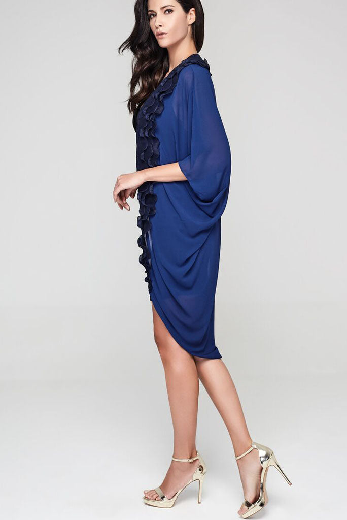 Model wearing navy blue kimono with a ruffle border facing left