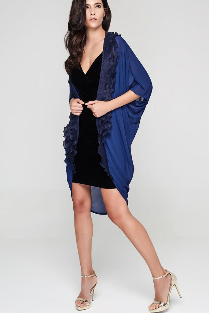 Model wearing navy blue kimono with a ruffle border facing sideways