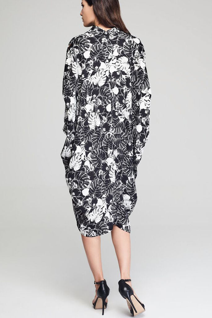 Model wearing black drape dress with white floral prints facing back