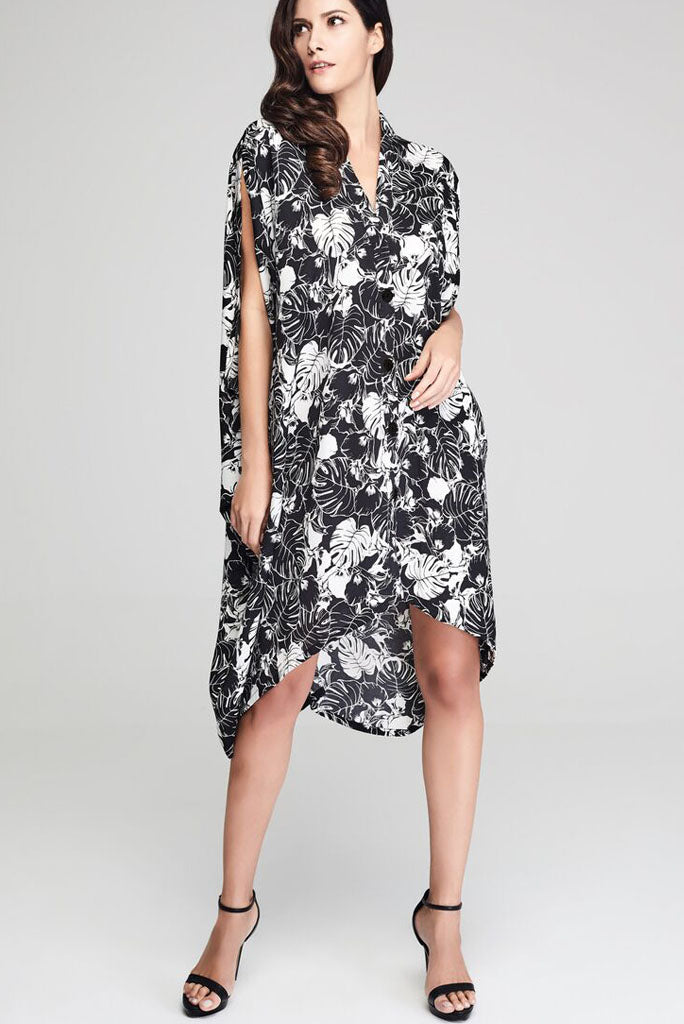 Model wearing black drape dress with white floral prints facing front