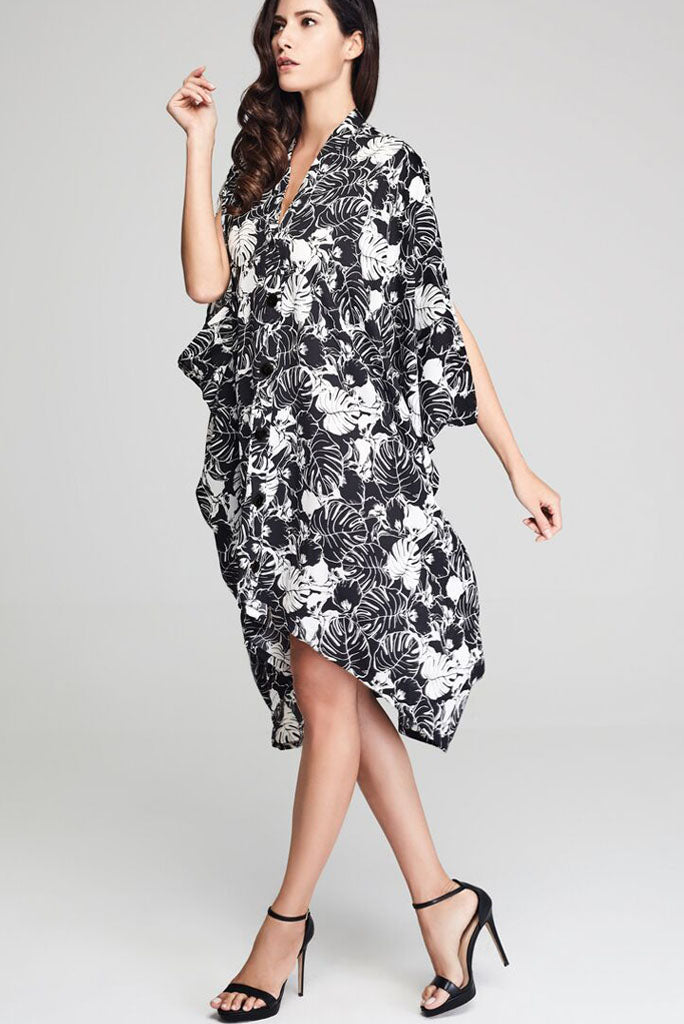 Model wearing black drape dress with white floral prints facing sideways