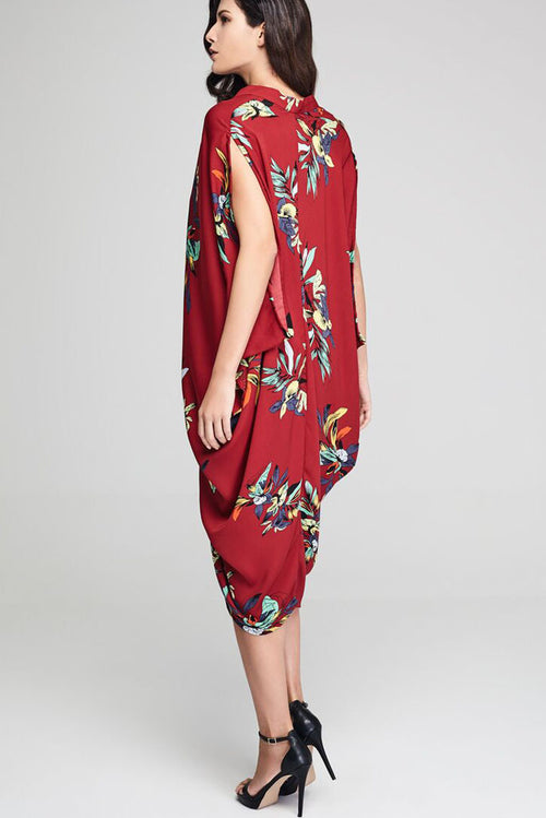 Model wearing red drape dress with floral prints facing sideways