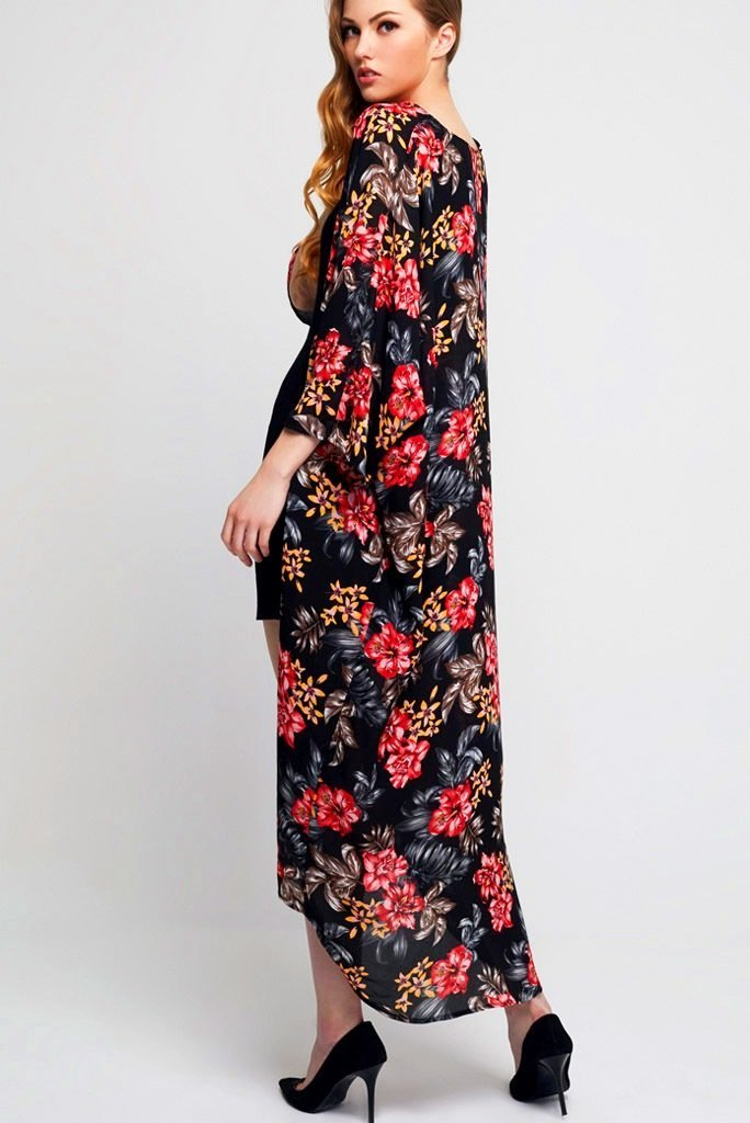 Model wearing long black crepe kimono with floral prints facing back