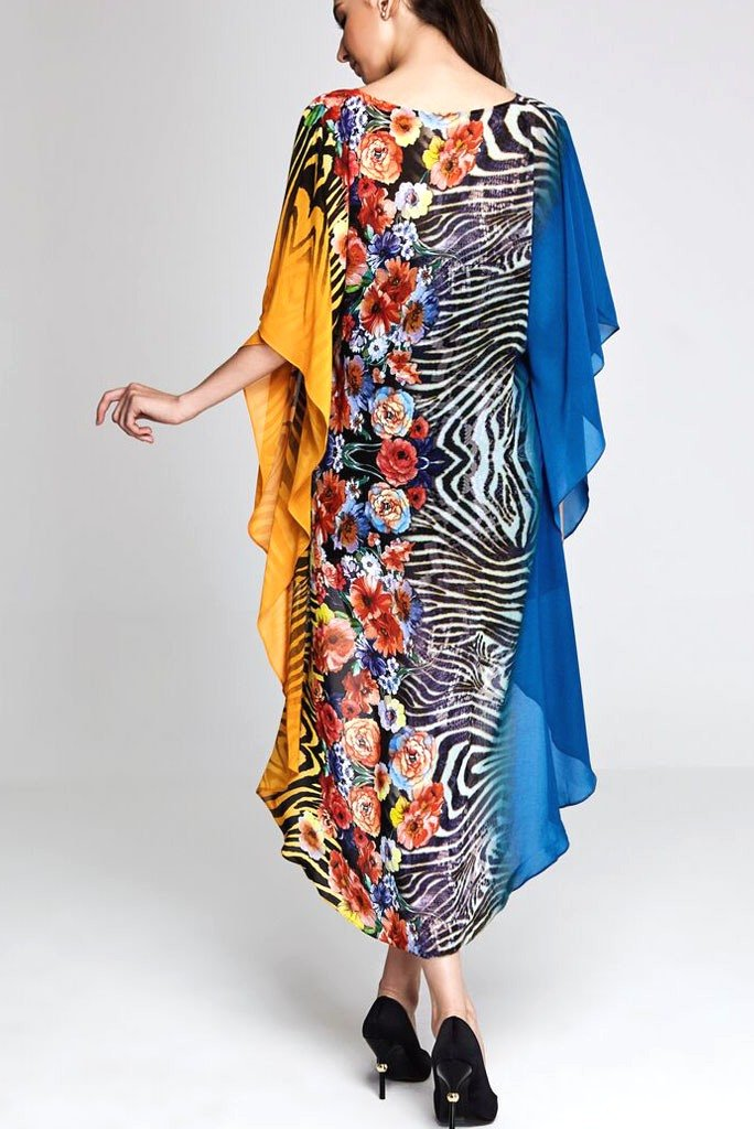 Model wearing blue & yellow hi-lo dress with floral prints facing backwards