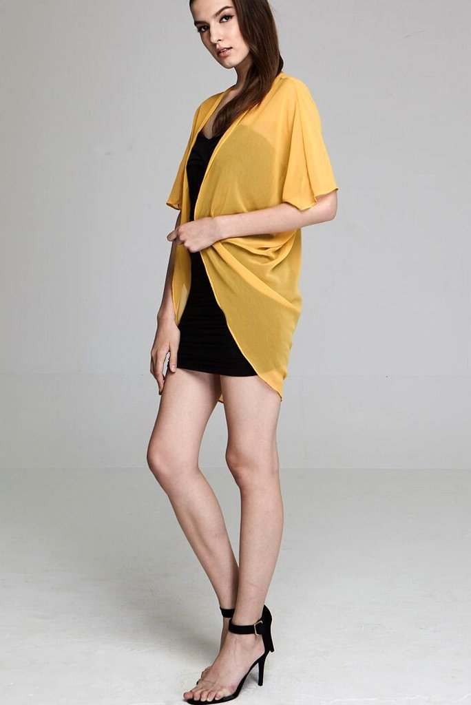 Model wearing short yellow chiffon kimono facing left