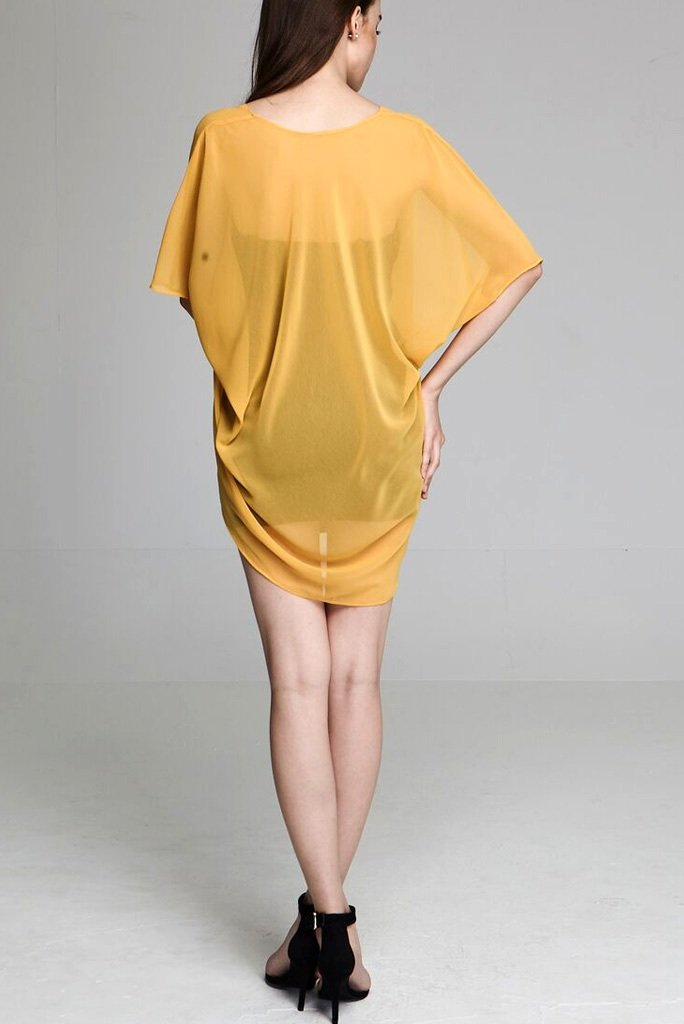 Model wearing short yellow chiffon kimono facing back