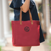 HBG monogrammed on a red tote bag being carried by a woman in a blue dress on a sunny day.