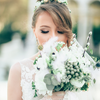 Bride in white dress with floral hair wreath and matching bouquet smells flowers.