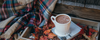 hot chocolate centered in this fall scene. Features orange and red leaves and a plaid blanket in a wooden box representing fall.