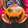 Painted orange and black pumpkin with scary face being held in little girl's hands