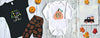 black t-shirt with witches boots and orange leggings. Orange pumpkin shirt with monogram. Brown truck with checkered pumpkin in the back with orange checkered wheels on a white t-shirt. Wooden background with pumpkins and leaves.