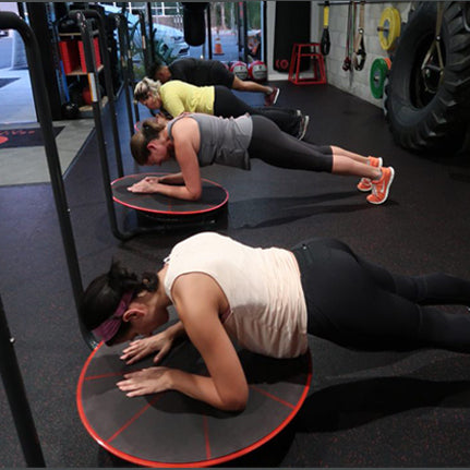 Group of people all performing plank exercise on their own Core-Tex Reactive Trainer