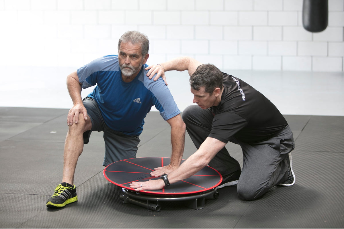 Older man performing exercise on the Core-Tex Reactive Trainer while being assisted by a trainer