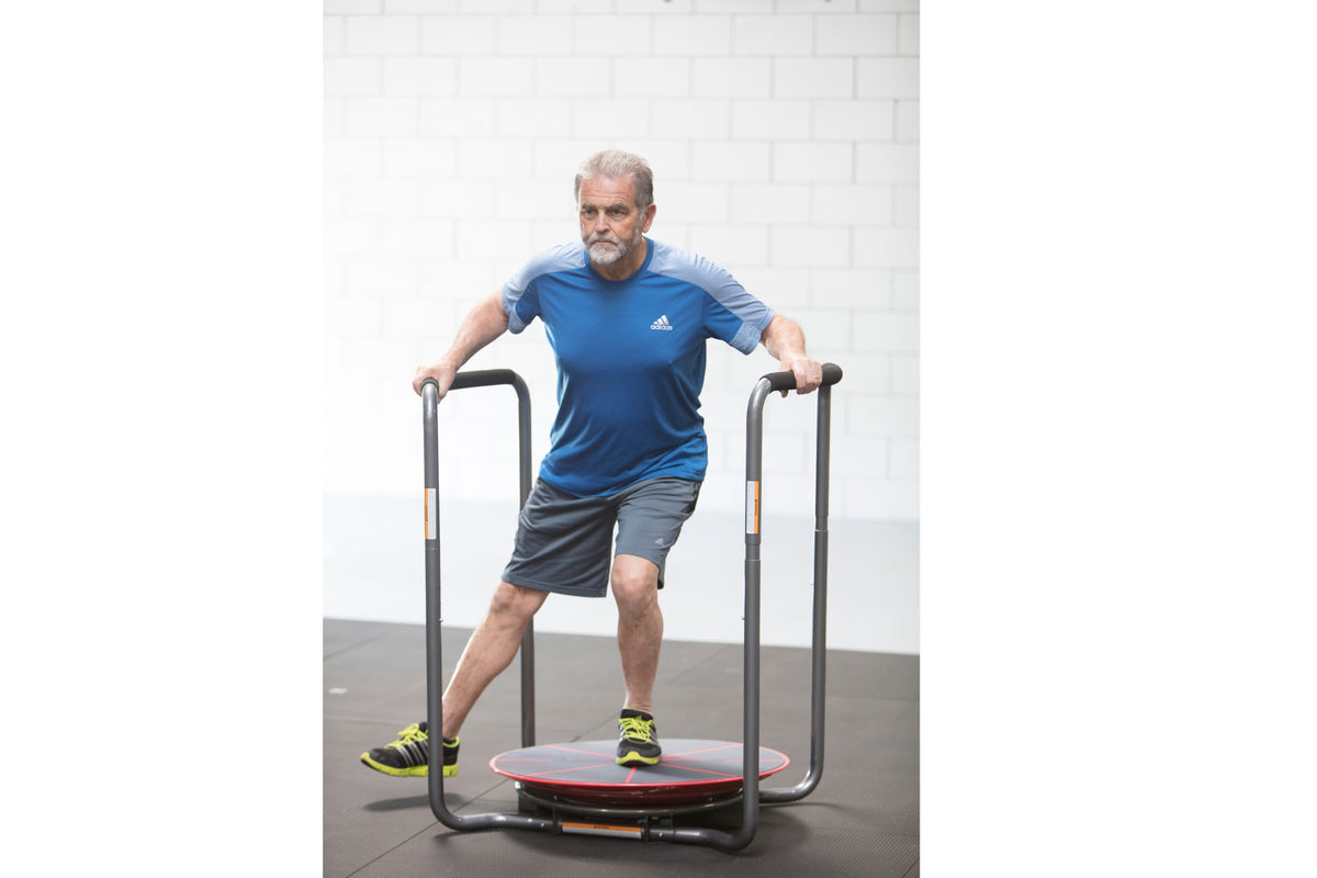 Older man exercising using the red Core-Tex Reactive Trainer with duel handrails