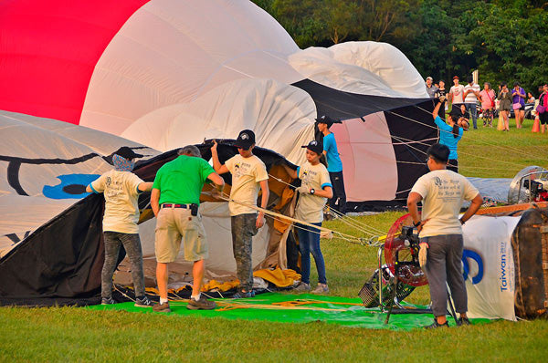 A crew helps inflate a hot air balloon with the assistance of a Ventry Fan