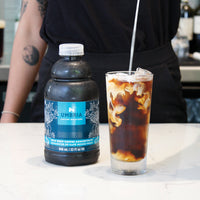 coffee concentrate bottle, glass of cold brew coffee with milk pouring in