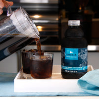 coffee concentrate bottle and two glasses on tray, pitcher is pouring cold brew into glass