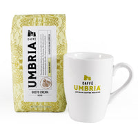 a cream colored coffee bag with gold highlights and white bistro coffee mug
