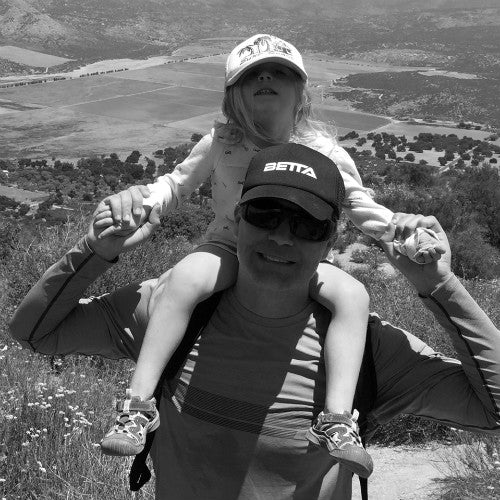 father hiking with daughter on shoulders