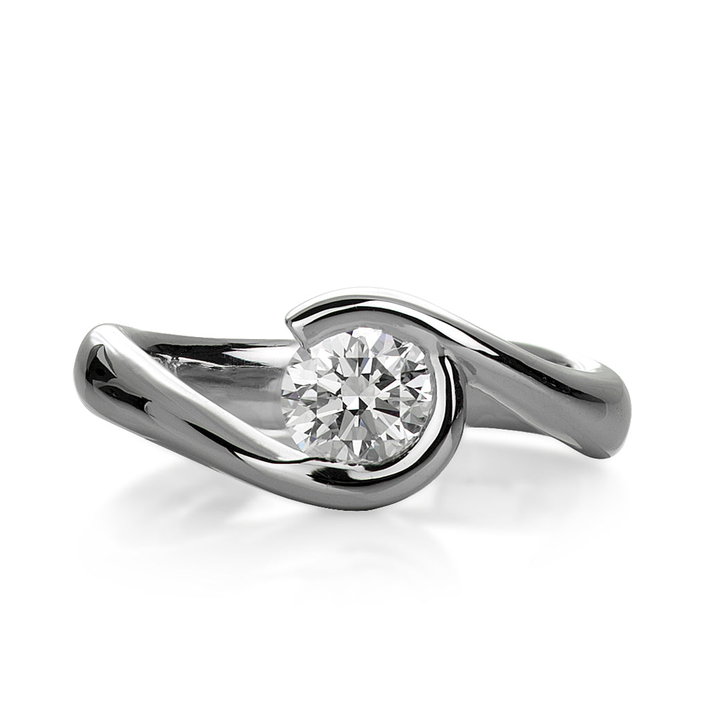 a fluid sweep of 18k white gold capturing this round diamond in a custom engagement ring designed by Davidson Jewels