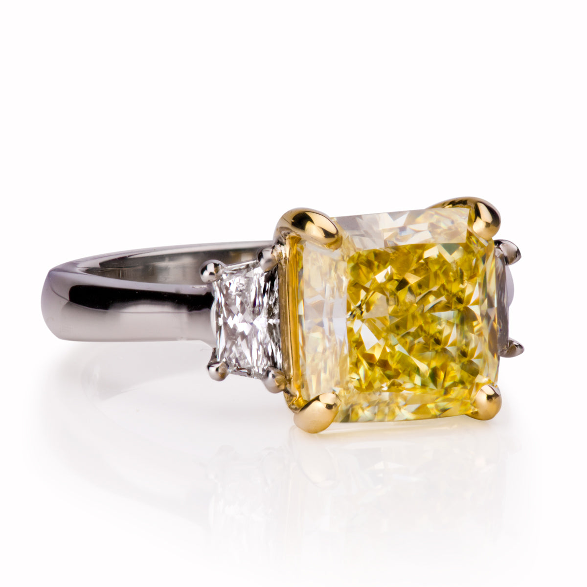 3 stone diamond ring with radiant cut fancy yellow diamond accented with 2 trapezoid cut white diamonds created by Davidson Jewels
