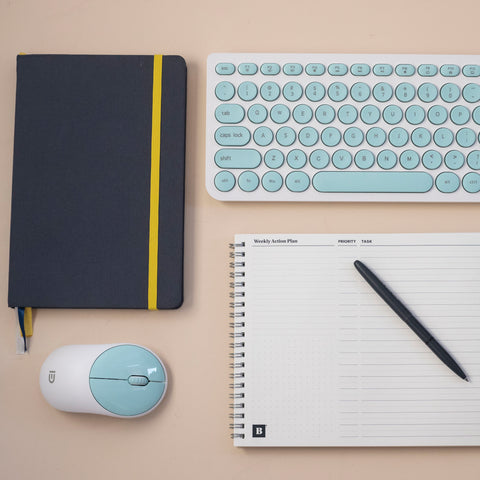 Weekly Action Pad blank with win the day pen, Self Journal, keyboard, and mouse on desk