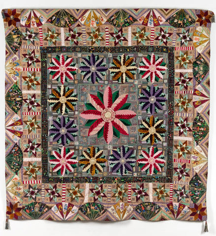 an ornate quilt made in 1887 from velvets with log cabin flowers and embroidered fans to the edges