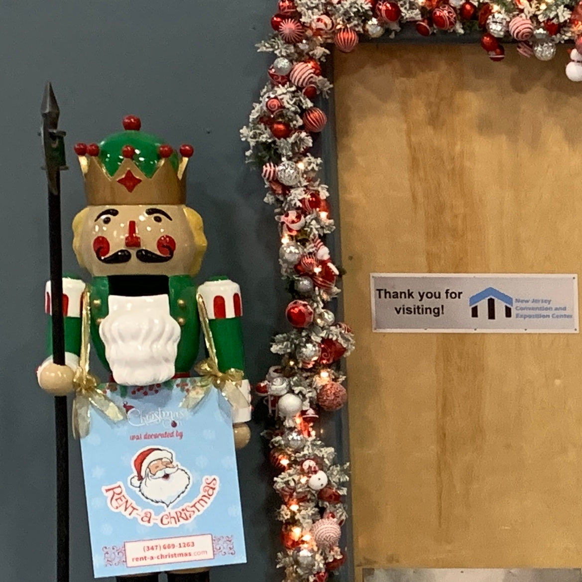 A lifesize nutcracker with a Rent-A-Christmas sign draped around his neck, and decorated garland