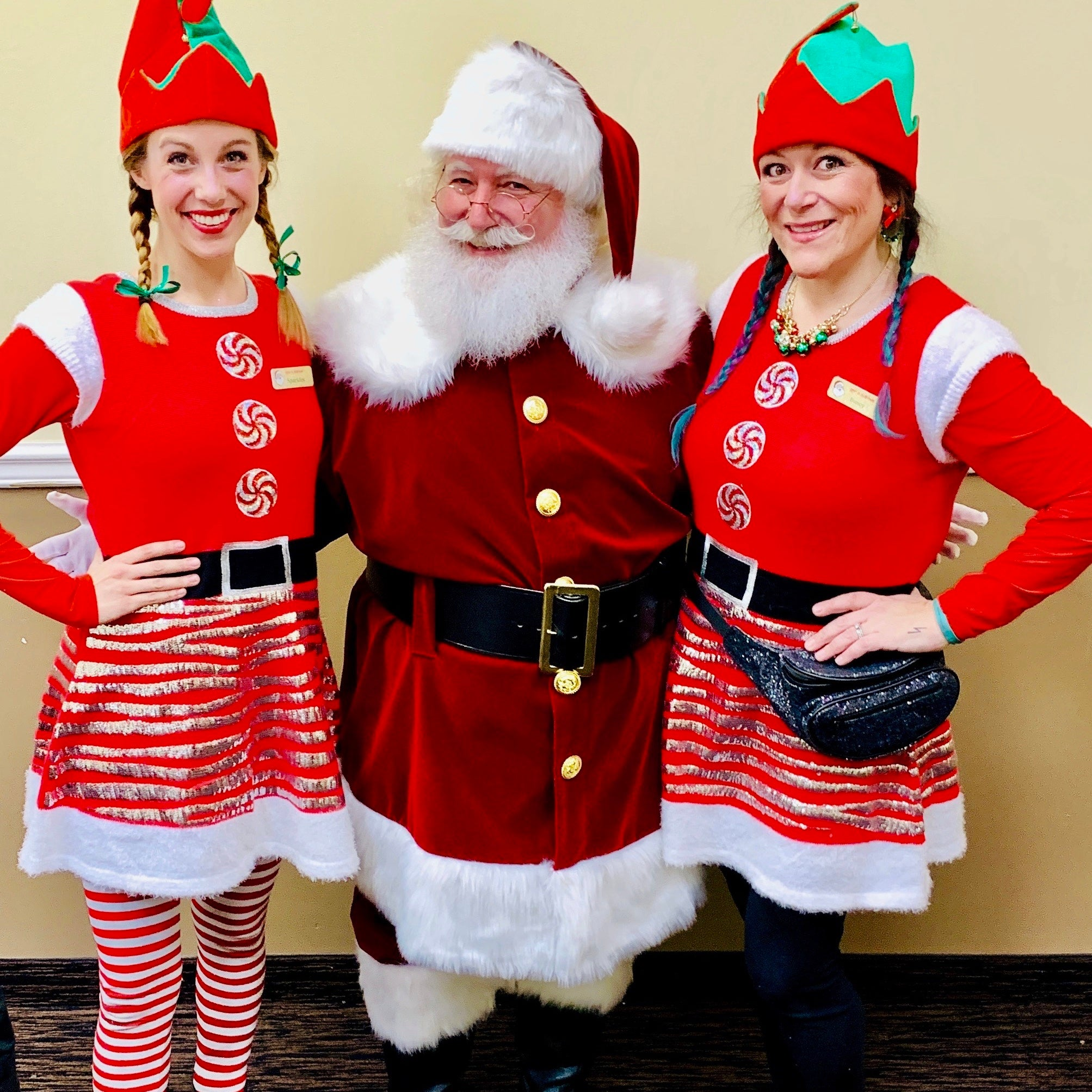 Two Rent-A-Christmas Elves posing with Santa Claus