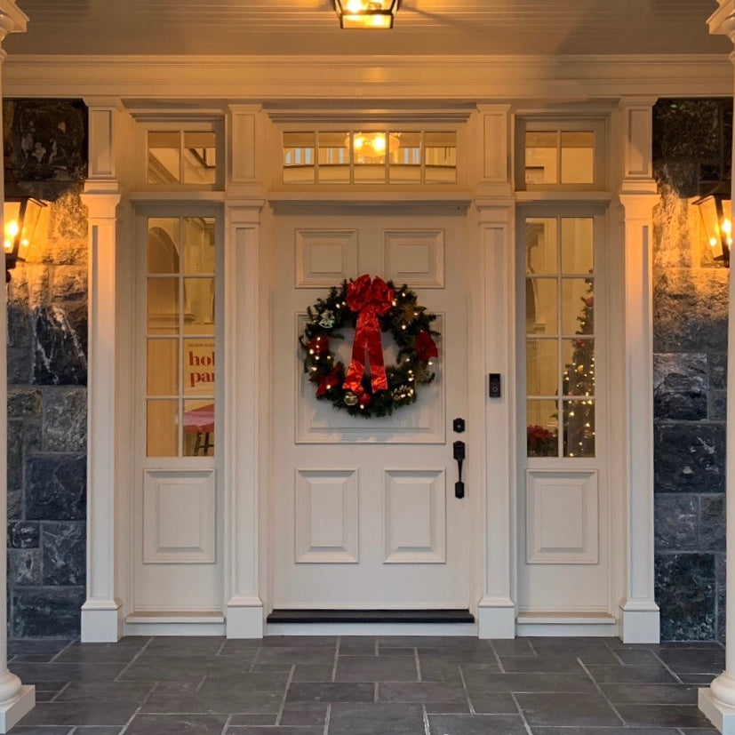 Decorated fresh-cut Christmas wreath hanging on residential exterior door