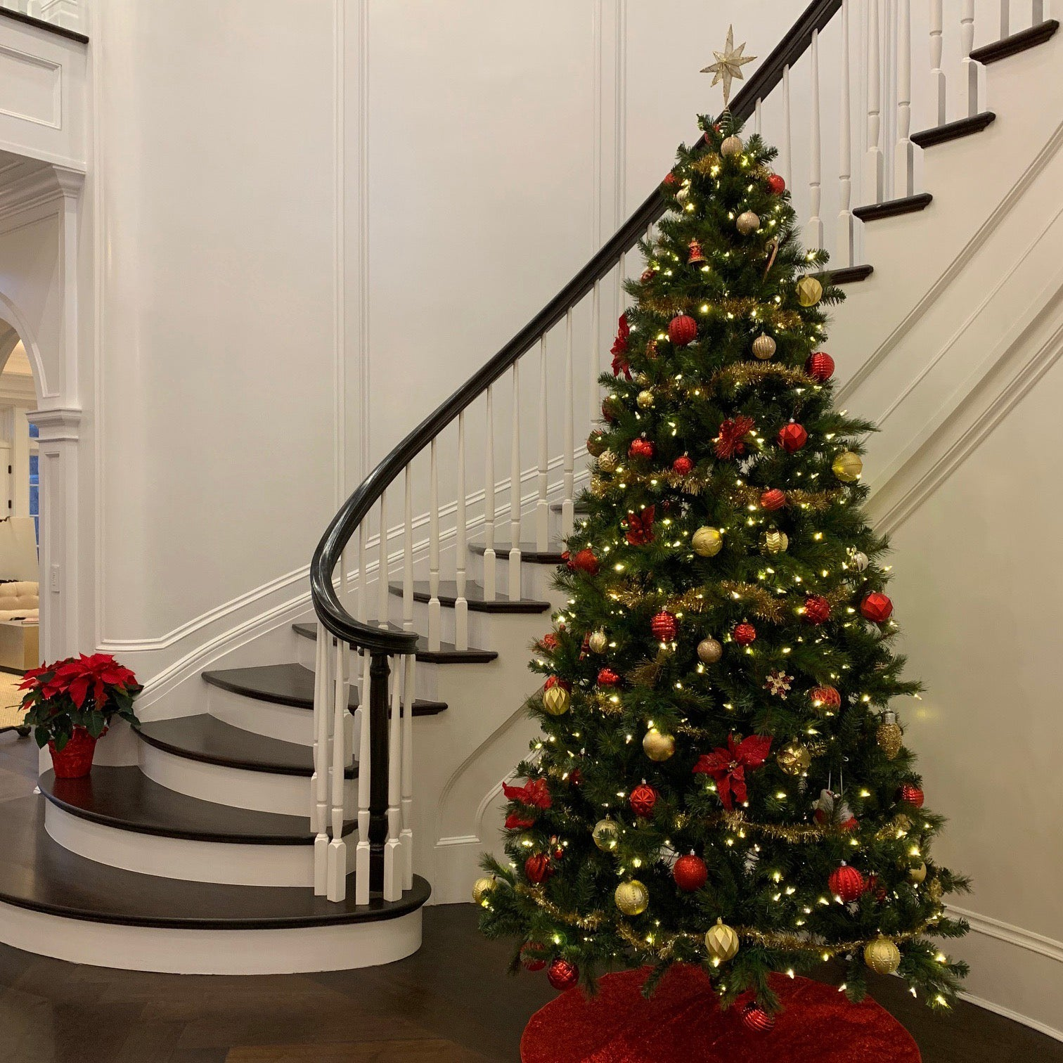 Decorated artificial Christmas tree by residential staircase